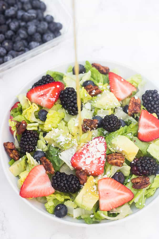This red, white, blue summer berry salad is loaded with fresh fruit, topped with avocado slices, feta cheese, & candied nuts, and drizzled with a naturally-sweetened lemon poppyseed dressing